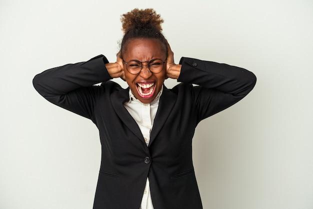 흰색 배경에 격리된 젊은 비즈니스 아프리카계 미국인 여성은 너무 큰 소리를 듣지 않으려고 손으로 귀를 막고 있습니다.