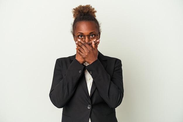 흰색 배경에 격리된 젊은 비즈니스 아프리카계 미국인 여성은 손으로 입을 가리고 충격을 받았습니다.