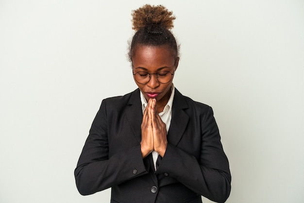 Young business african american woman isolated on white background holding hands in pray near mouth, feels confident.