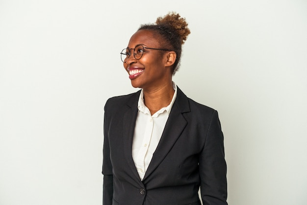 Young business african american woman isolated on white background looks aside smiling, cheerful and pleasant.