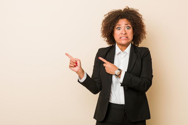 Young business african american woman shocked pointing with index fingers to a copy space.