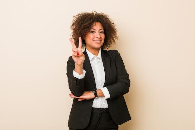 若いビジネスアフリカ系アメリカ人女性の指で数2を示します。