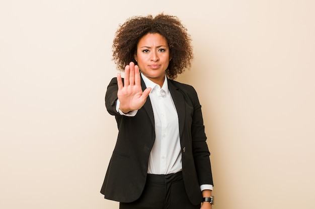Young business african american woman standing with outstretched hand showing stop sign, preventing you.