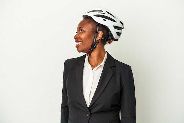 Young business african american woman wearing a bike helmet isolated on white background looks aside smiling, cheerful and pleasant.