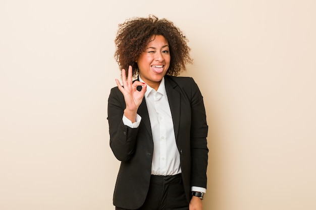 Young business african american woman winks an eye and holds an okay gesture with hand.