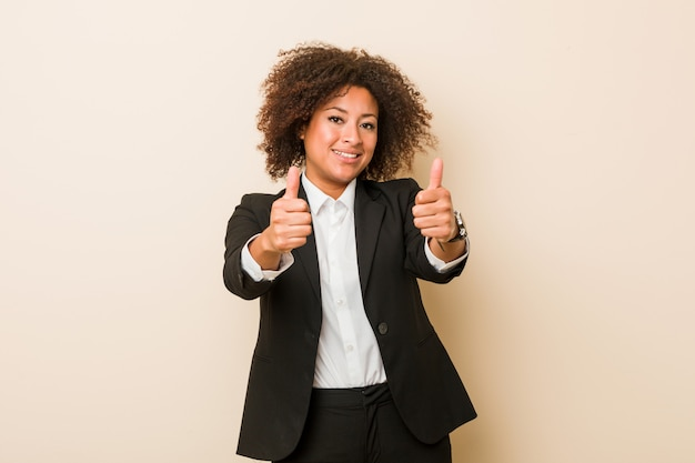 Young business african american woman with thumbs ups, cheers about something, support and respect concept.
