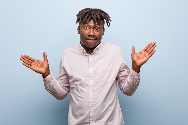 Молодой деловой африканский черный человек смущен и сомневается, поднимая ему руки, чтобы держать копию пространства.