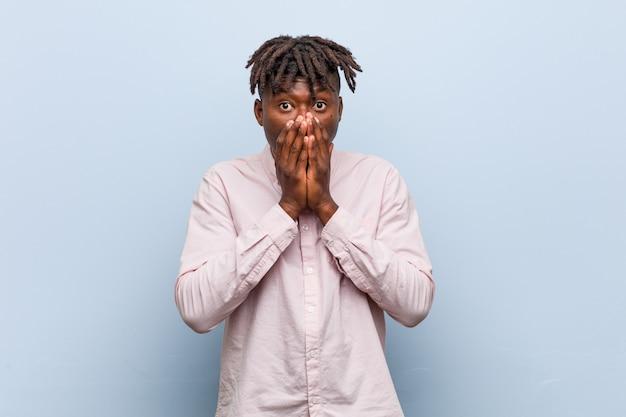 何かについて笑って、手で口を覆っている若いビジネスアフリカ黒人男性。