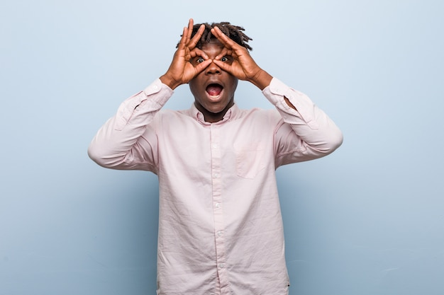 Young business african black man showing okay sign over eyes