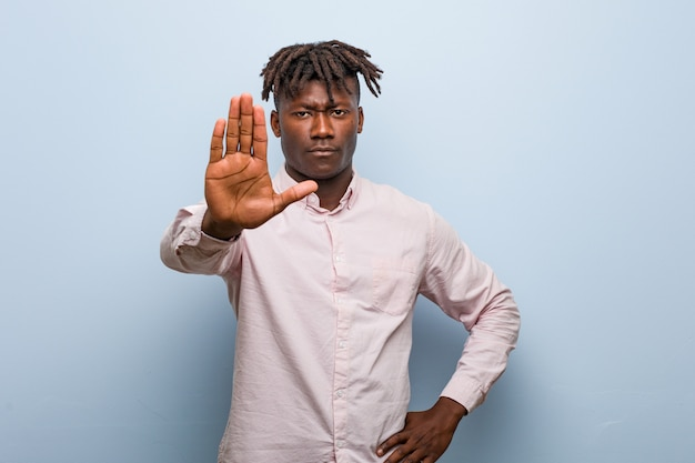 Young business african black man standing with outstretched hand showing stop sign, preventing you.