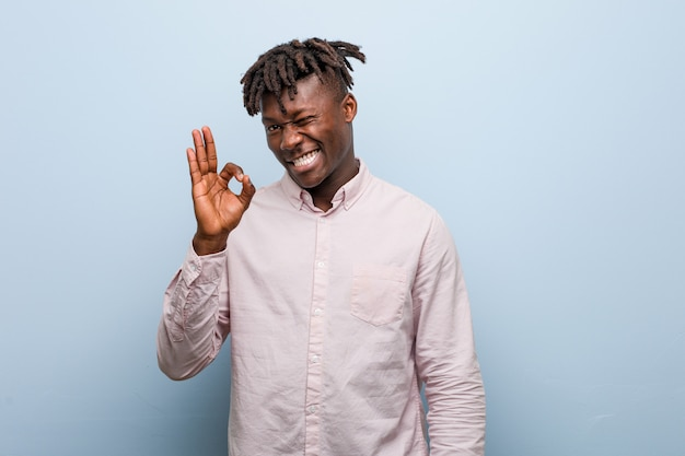 Young business african black man winks an eye and holds an okay gesture with hand.