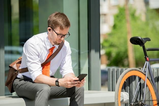 近くに自転車を持ってモダンな建物のベンチに座って、スマートフォンでクライアントとの約束をする若いビジネスエージェント