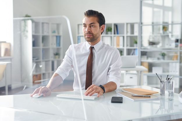 Young business analyst looking at computer screen while looking through online data