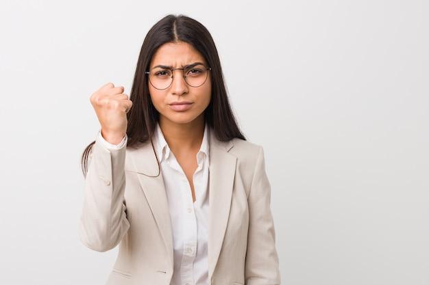 Женщина молодого дела арабская изолированная против белой стены показывая кулак к с агрессивным выражением лица.