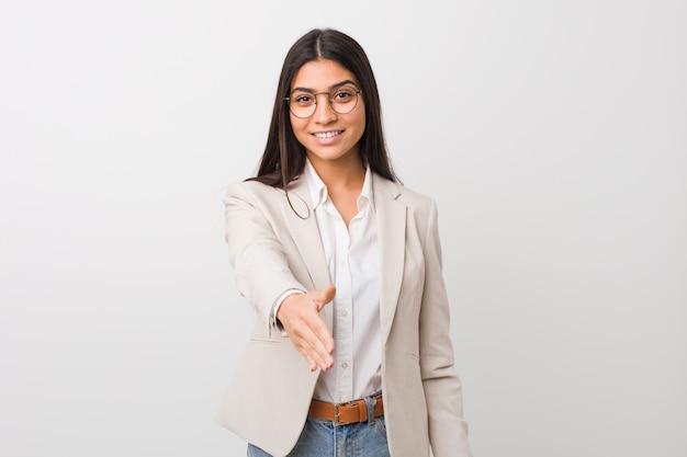 ジェスチャーを挨拶で手を伸ばして白い壁に対して隔離される若いビジネスアラブ女性。