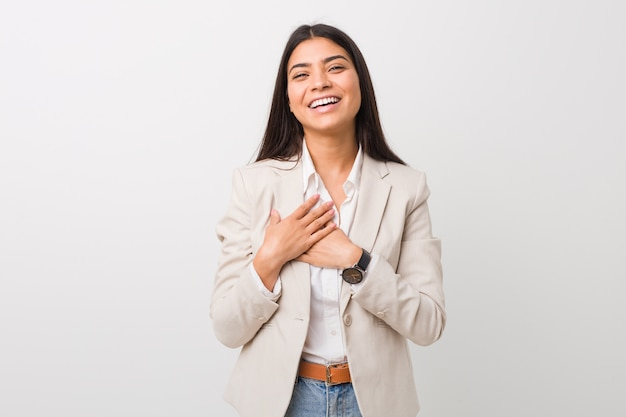 Young business arab woman isolated against a white background laughing keeping hands on heart, concept of happiness.