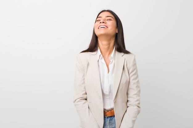 Young business arab woman isolated against a white wall relaxed and happy laughing, neck stretched showing teeth.