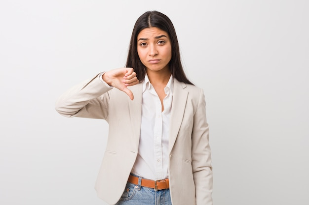 Young business arab woman isolated against a white wall showing a dislike gesture, thumbs down. disagreement concept.