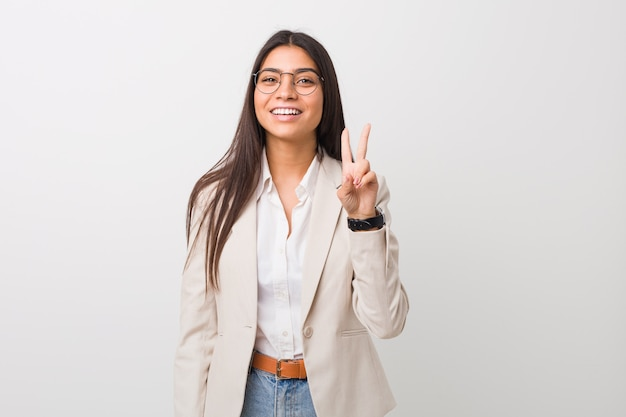 Young business arab woman isolated against a white wall showing victory sign and smiling broadly.