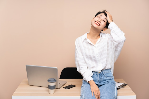 Young business asian girl in her workplace laughing