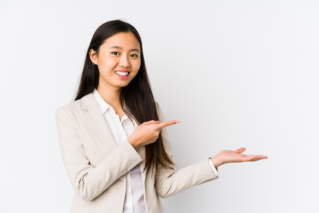 Young business asian woman excited holding something on palm