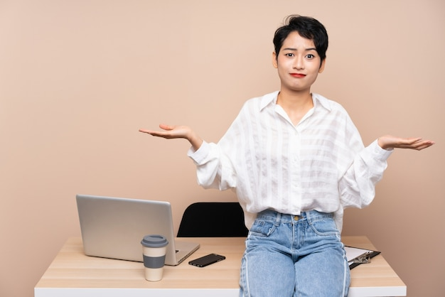 Young business asian woman in her workplace having doubts with confuse face expression