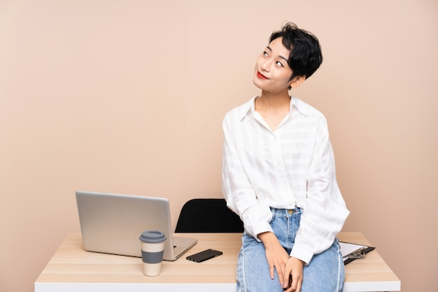 Young business asian woman in her workplace laughing and looking up