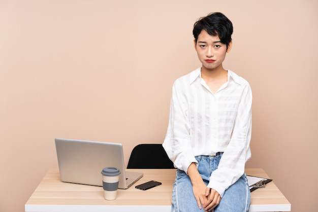 Young business asian woman in her workplace sad