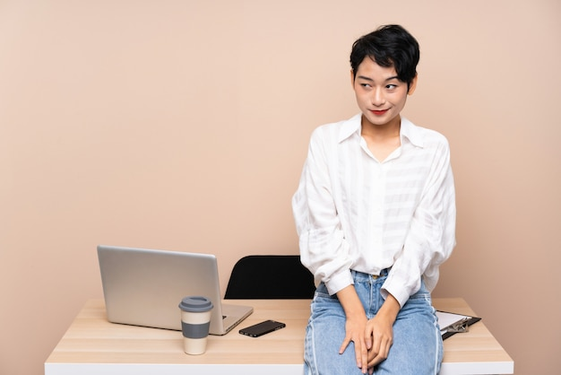 Young business asian woman in her workplace standing and looking to the side