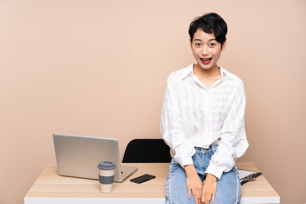 Young business asian woman in her workplace with surprise facial expression