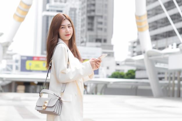 クリーム色のスーツを着た若いビジネスアジア人女性は、オフィスで働く間、屋外で携帯電話(スマートフォン)を使用してパートナーと連絡を取り合っています。