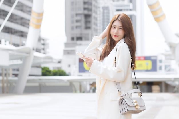 携帯電話のスマートフォンを使用してカメラを見てクリーム色のスーツを着た若いビジネスアジアの女性