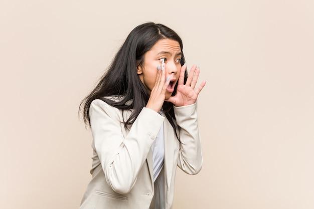 Молодой бизнес азиатская женщина кричит громко, держит глаза открытыми и руки напряжены