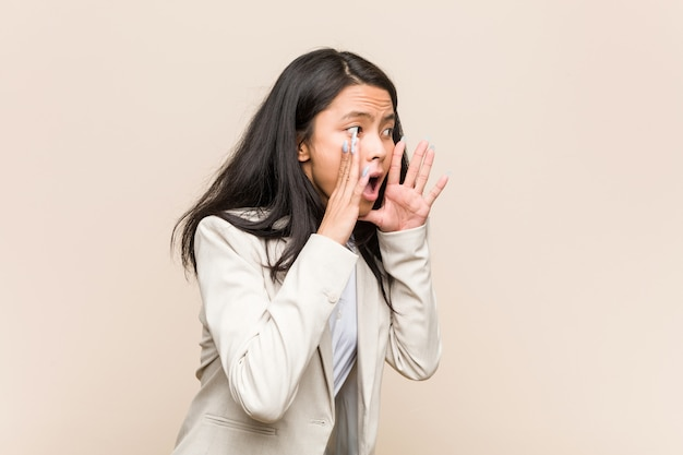 Young business asian woman shouts loud, keeps eyes opened and hands tense