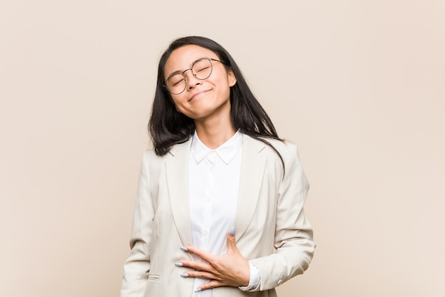 Young business asian woman touches tummy, smiles gently
