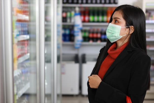 Young business asian woman wearing face mask looking and choosing grocery to buy from shelf in supermarket department store or shopping mall