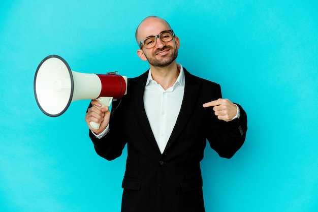 Молодой деловой лысый мужчина держит мегафон изолированного человека, указывая рукой на пространство для копирования рубашки, гордый и уверенный