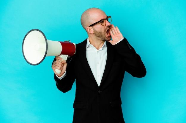 Молодой деловой лысый мужчина, держащий мегафон, кричит и держит ладонь возле открытого рта.