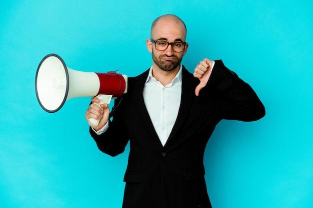 Молодой деловой лысый мужчина, держащий мегафон, показывает жест неприязни, пальцы вниз. концепция несогласия.