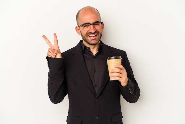 Young business bald man holding take away coffee isolated on white background  joyful and carefree showing a peace symbol with fingers.