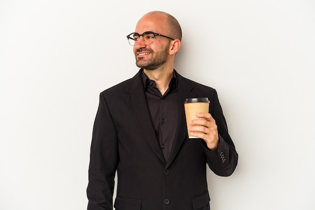 Young business bald man holding take away coffee isolated on white background  looks aside smiling, cheerful and pleasant.