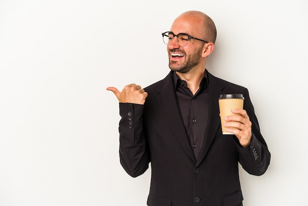 Young business bald man holding take away coffee isolated on white background  points with thumb finger away, laughing and carefree.