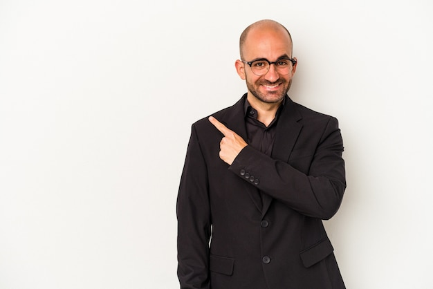 Young business bald man isolated on white background  smiling and pointing aside, showing something at blank space.