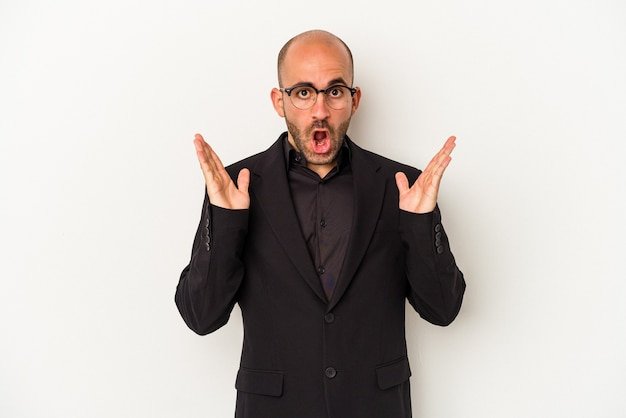 Young business bald man isolated on white background  surprised and shocked.