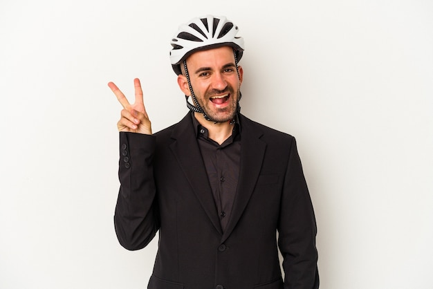 Young business bald man wearing a bike helmet isolated on white background  joyful and carefree showing a peace symbol with fingers.