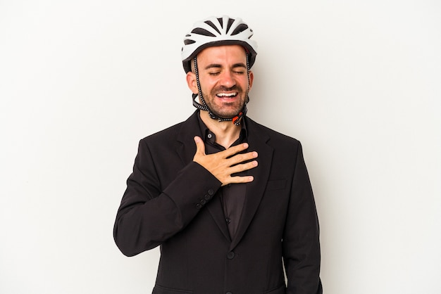 Young business bald man wearing a bike helmet isolated on white background  laughs out loudly keeping hand on chest.