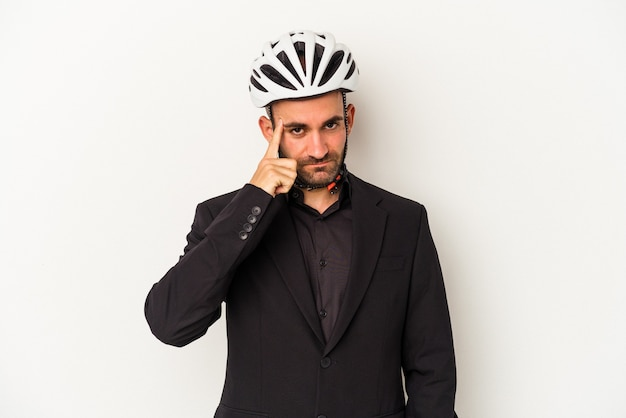 Young business bald man wearing a bike helmet isolated on white background  pointing temple with finger, thinking, focused on a task.