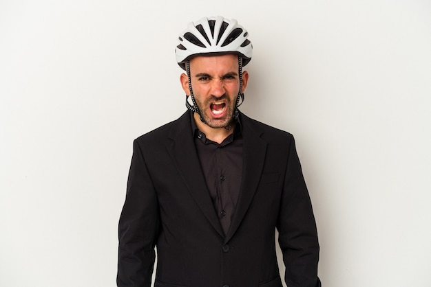 Young business bald man wearing a bike helmet isolated on white background  screaming very angry and aggressive.