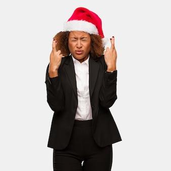 Чернокожая женщина молодого дела нося пальцы скрещивания шляпы santa chirstmas для везения Premium Фотографии