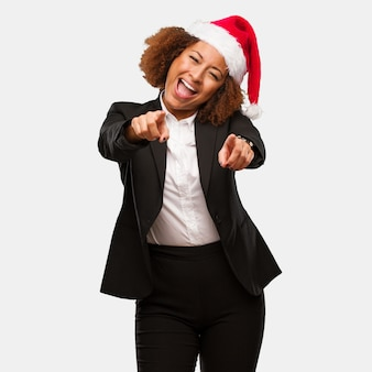 Young business black woman wearing a chirstmas santa hat cheerful and smiling